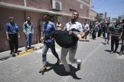 A Palestinian man rushes wounded woman into hospital in southern Gaza Strip.