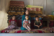 A young Yazidi woman sits with her three children inside a tent for displaced persons in northern Iraq on May 28, 2017. They fled the 2014 ISIS advance in which many Yazidis were killed and others, especially women and children, captured and trafficked by ISIS. (iStock/Joel Carillet)