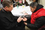 TURNING TOWARD MORNING. Archbishop Blase J. Cupich of Chicago blesses a rosary for Jaime Dones as he visited with patrons during a Thanksgiving dinner put on by Catholic Charities on Nov. 27, 2014. The dinner is held for the homeless and the hungry.