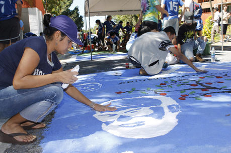 Ivette Escobar, a student at Central American University in San Salvador, helps finish a rug in honor of the victims in the 1989 murder of six Jesuits, their housekeeper and her daughter on the UCA campus, part of the 25th anniversary commemoration of the Jesuit martyrs in 2014. (CNS photo/Edgardo Ayala)