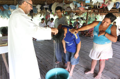 Augustinian Father Miguel Angel Cadenas baptizes a young man June 12, in a village along the Urituyacu River in Peru.