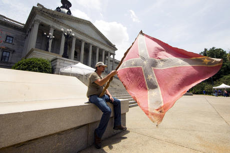 A man holds a Confederate flag outside the Statehouse in Columbia, S.C., on July 9, 2015, hours before Gov. Nikki Haley signed a bill to remove the flag from Statehouse grounds. (CNS photo/Jason Miczek, Reuters)