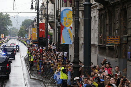 A banner showing St. John Paul II hangs from a lamp pole in Krakow, Poland, as Pope Francis arrives to attend World Youth Day in 2016. Surveys show that Poland leads Europe, and the United States, in religious commitment. (CNS photo/Paul Haring)