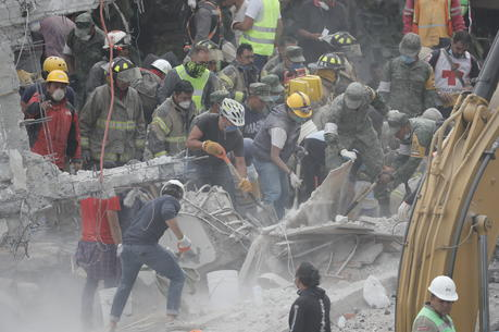 Rescue workers search for survivors in the debris of collapsed buildings Sept. 20 in Mexico City. The magnitude 7.1 earthquake hit Sept. 19 to the southeast of the city, killing hundreds. (CNS photo/Jose Mendez, EPA)