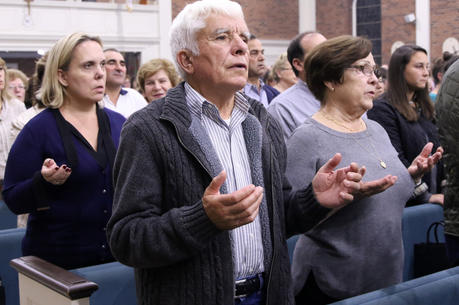 Worshippers recite the Lord's Prayer during Mass at Corpus Christi Church in Mineola, N.Y., on Oct. 13. (CNS photo/Gregory A. Shemitz, Long Island Catholic)