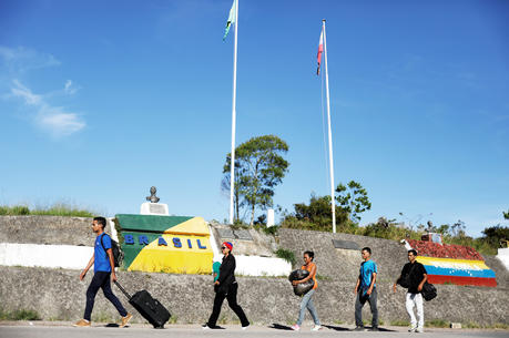 Venezuelan migrants walk across the border from Venezuela into the Brazilian city of Pacaraima. (CNS photo/Nacho Doce)