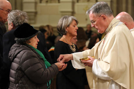 Retired New York Auxiliary Bishop Gerald T. Walsh distributes Communion during a Mass on the March 17 feast of St. Patrick, patron of the Archdiocese of New York, at St. Patrick's Cathedral in New York City. (CNS photo/Gregory A. Shemitz)