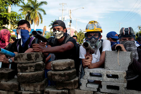 Demonstrators in Managua, Nicaragua, stand behind a barricade during clashes with police May 30. (CNS photo/Oswaldo Rivas, Reuters)