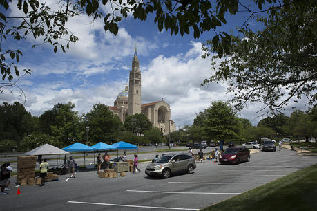 Catholic Charities staff and volunteers in the Archdiocese of Washington distribute 500 grocery boxes and 500 family meals in the parking lot of the Basilica of the National Shrine of the Immaculate Conception July 10, 2020, during the coronavirus pandemic. (CNS photo/Tyler Orsburn)