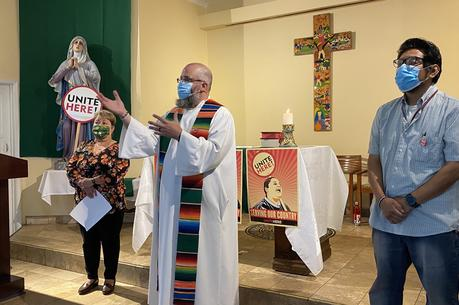 Brendon Busse, S.J., center, celebrates a Mass at Dolores Mission Church in Los Angeles on June 20 for hospitality workers to view online. (Courtesy Unite Here Local 11)