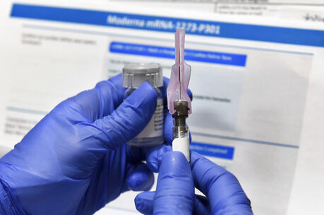 A nurse prepares a shot as a study of a possible Covid-19 vaccine, developed by the National Institutes of Health and Moderna Inc., on July 27 in Binghamton, N.Y. (AP Photo/Hans Pennink)