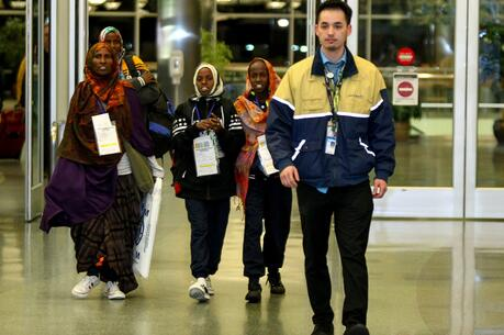Somali refugees are escorted by a United Airlines representative as they arrive at the airport on Feb. 13, 2018, in Boise, Idaho. (CNS photo/Brian Losness, Reuters)