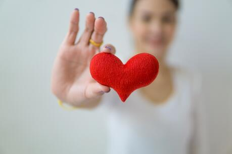 A woman, blurred out in the background, holds a red heart made of felt-like material in the foreground of the photo