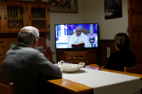 "People watch television at a home in Cisternino, Italy, as Pope Francis gives his extraordinary blessing ""urbi et orbi"" (to the city and the world) from the atrium of St. Peter's Basilica at the Vatican March 27, 2020. The blessing was livestreamed because of the coronavirus pandemic. (CNS photo/Alessandro Garofalo, Reuters)"