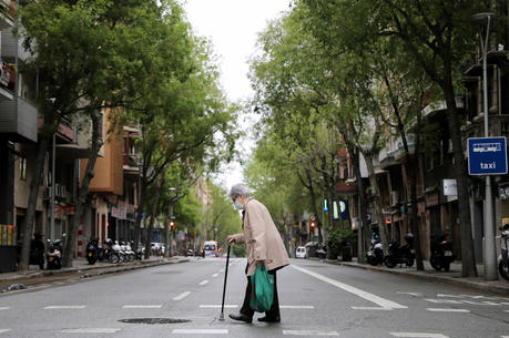 An elderly woman wears a protective face mask as she walks with shopping bags during the COVID-19 pandemic in Barcelona, Spain, April 1, 2020. (CNS photo/Nacho Doce, Reuters)