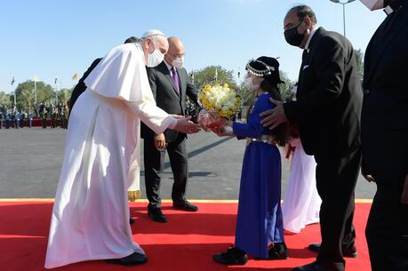 Pope Francis receives flowers from children during a welcoming ceremony with Iraqi President Barham Salih at the presidential palace in Baghdad on March 5, 2021. (CNS photo/Vatican Media)