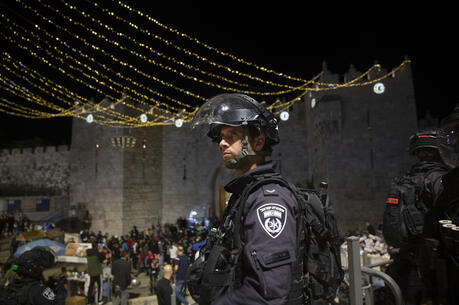 An Israeli police officer stands guard at the Damascus Gate to the Old City of Jerusalem after clashes at the Al-Aqsa Mosque compound, Friday, May 7, 2021. Palestinian worshippers clashed with Israeli police late Friday at the holy site sacred to Muslims and Jews, in an escalation of weeks of violence in Jerusalem that has reverberated across the region. (AP Photo/Maya Alleruzzo)