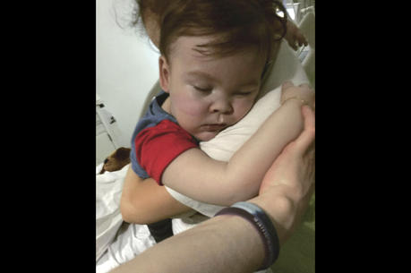 Brain-damaged toddler Alfie Evans cuddles his mother Kate James at Alder Hey Hospital, Liverpool, England.