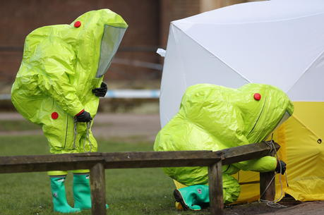 Personnel in hazmat suits work to secure a tent over the bench in Salisbury where former Russian double agent Sergei Skripal and his daughter Yulia were found critically ill by exposure to a nerve agent on March 4. (Andrew Matthews/PA via AP)