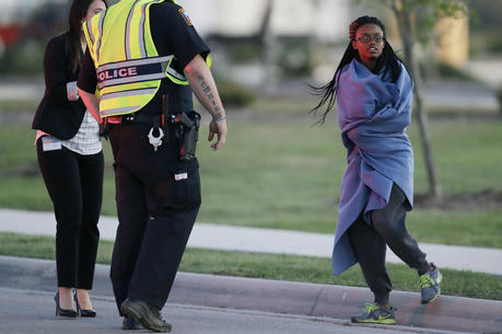 An employee wrapped in a blanket talks to a police officer after she was evacuated at a FedEx distribution center where a package exploded on March 20, 2018, in Schertz, Texas. (AP Photo/Eric Gay)