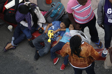 People wait to apply for asylum in the United States along the border on July 16 in Tijuana, Mexico. (AP Photo/Gregory Bull)