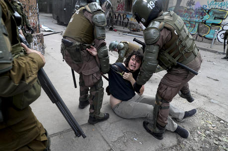 Police detain a demonstrator during an anti-government protest in Santiago, Tuesday, Nov. 5, 2019. Chileans have been taking to the streets and clashing with the police to demand better social services and an end to economic inequality, even as the government announced that weeks of demonstrations are hurting the country's economic growth. (AP Photo/Esteban Felix)