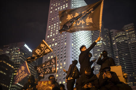 "A protestor holds a flag that reads: ""Liberate Hong Kong, Revolution of Our Times"" at a rally in Hong Kong on Dec. 12. Protesters wrote hundreds of Christmas cards for detainees jailed during the city's pro-democracy movement. (AP Photo/Mark Schiefelbein)"