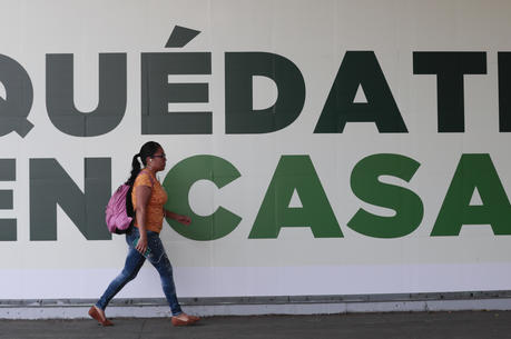 "In Mexico City on March 31 a woman walks past a sign that urges: ""Stay home."" Mexico's government broadened its shutdown of ""non essential activities"" and prohibited gatherings of more than 50 people to help slow down the spread of the new coronavirus. (AP Photo/Eduardo Verdugo)"