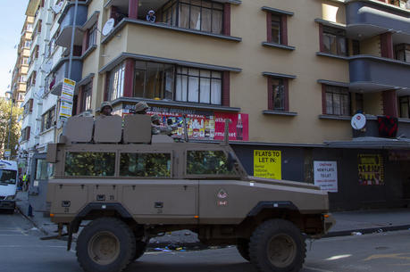 Residents stand on a balcony as a South African National Defence Forces vehicle patrol the street, in Johannesburg on April 7. South Africa and more than half of Africa's 54 countries have imposed lockdowns, curfews, travel bans or other restrictions to try to contain the spread of COVID-19. (AP Photo/Themba Hadebe)
