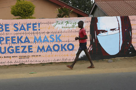 A young boy walks past a wall with graffiti urging people to wear face masks in Harare, on May 28. Manhunts have begun after hundreds of people fled quarantine centres in Zimbabwe and Malawi. Authorities worry they will spread COVID-19 in countries whose health systems can be rapidly overwhelmed. (AP Photo/Tsvangirayi Mukwazhi)