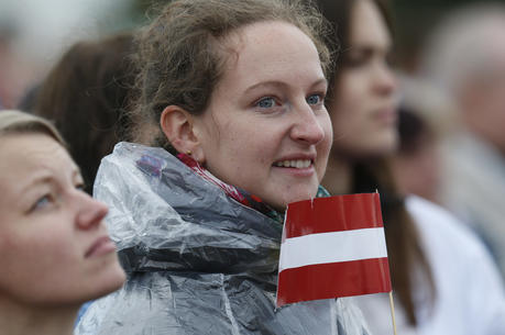 A young woman holds the Latvian flag as Pope Francis celebrates Mass Sept. 24 at the Shrine of the Mother of God in Aglona, Latvia. (CNS photo/Paul Haring)