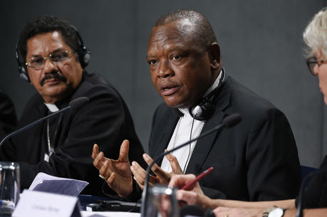 Cardinal Fridolin Ambongo Besungu of Kinshasa, Congo, speaks at a news conference after a session of the Synod of Bishops for the Amazon at the Vatican Oct. 22, 2019. At left is Bishop Karel Choennie of Paramaribo, Suriname. (CNS photo/Paul Haring)