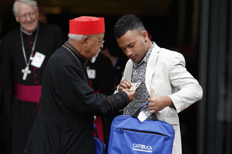 Ethiopian Cardinal Berhaneyesus Souraphiel of Addis Ababa checks out the name badge of Nathanael Lamataki, a youth delegate from the French territory of New Caledonia in the South Pacific, as they leave a session of the Synod of Bishops on young people, the faith and vocational discernment at the Vatican Oct. 5. (CNS photo/Paul Haring)