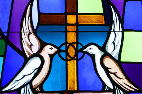 Doves and interlocking wedding bands symbolizing the sacrament of marriage are depicted in a stained-glass window at Sts. Cyril & Methodius Church in Deer Park, N.Y.