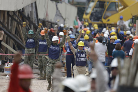Soldiers hold up closed fists motioning for silence during rescue efforts at the Enrique Rebsamen school in Mexico City, Mexico, on Sept. 21. (AP Photo/Rebecca Blackwell)