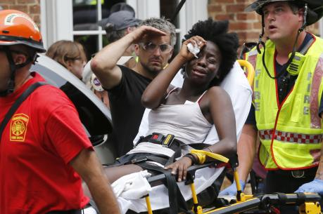 Rescue personnel help an injured woman after a car ran into a large group of protesters after an white nationalist rally in Charlottesville, Va., on Aug. 12. (AP Photo/Steve Helber)