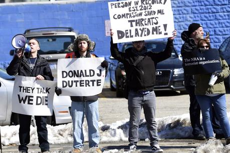Protesters gather near the Manchester Central Fire Station in Manchester, N.H., Monday, March 19, 2018, where President Donald Trump madee an unscheduled visit. Trump is in New Hampshire to unveil more of his plan to combat the nation's opioid crisis. (AP Photo/Susan Walsh)