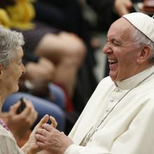 Pope Francis laughs as he greets a woman during an audience with people from Lyon, France, in Paul VI hall at the Vatican July 6. The audience was with 200 people living in difficult or precarious situations. (CNS photo/Paul Haring)