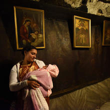 A pilgrim from India holds her baby in front of a painting of the Mary and the Christ Child in the grotto of the Church of Nativity in Bethlehem. (CNS photo/Debbie Hill)