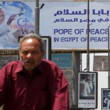 A man rides a bicycle past a billboard with an image of Pope Francis April 26 ahead of the pontiff's April 28-29 visit to Cairo. (CNS photo/Amr Abdallah Dalsh, Reuters)
