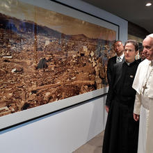 Pope Francis walks by a photo showing the destruction of an atomic bomb during a visit to the Jesuit-run Sophia University in Tokyo on Nov. 26, 2019. (CNS photo/Vatican Media via Reuters)