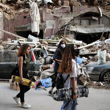 Women walk past destroyed cars at a neighborhood near the scene of Tuesday's explosion that hit the seaport of Beirut, Lebanon, Friday, Aug. 7, 2020. Rescue teams were still searching the rubble of Beirut's port for bodies on Friday, nearly three days after a massive explosion sent a wave of destruction through Lebanon's capital. (AP Photo/Thibault Camus)