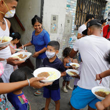 Haitians and Venezuelans receive food aid from church members in Lima, Peru, March 30, 2020. (CNS photo/Sebastian Castaneda, Reuters)