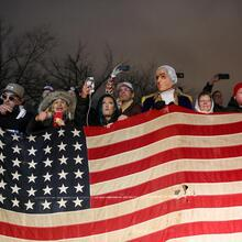 People without masks hold an American flag next to a bust of George Washington doing the same