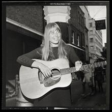Joni Mitchell strums guitar outside the The Revolution Club, London, England, Sept. 17, 1968 (Alamy).