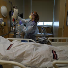 Registered nurse Nikki Hollinger cleans up a room as a body of a COVID-19 victim lies in a body bag labeled with stickers at Providence Holy Cross Medical Center in the Mission Hills section of Los Angeles, Saturday, Jan. 9, 2021. The U.S. death toll from the coronavirus has eclipsed 400,000 in the waning hours in office for President Donald Trump. (AP Photo/Jae C. Hong)