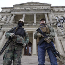 Armed men stand on the steps at the State Capitol after a rally in support of President Donald Trump in Lansing, Mich., on Jan. 6, 2021. (AP Photo/Paul Sancya, File)