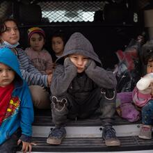 Migrant children from Central America take refuge from the rain in the back of a U.S. Border Patrol vehicle in Penitas, Texas, March 14, 2021, as they await to be transported after crossing the Rio Grande into the United States. (CNS photo/Adrees Latif, Reuters)