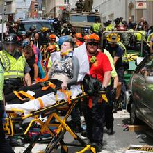 Rescue personnel help injured people after a car ran into a large group of protesters after a white nationalist rally in Charlottesville, Va., on Aug. 12, 2017. One person was killed and 19 were injured in the incident. (AP Photo/Steve Helber)