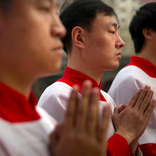 In this March 31, 2018, file photo, Chinese acolytes pray during a Holy Saturday Mass on the evening before Easter at the Cathedral of the Immaculate Conception, a government-sanctioned Catholic church in Beijing. (AP Photo/Mark Schiefelbein, File)